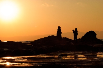 Silhouette of a man taking a sunset photo while a young girl looks on.
