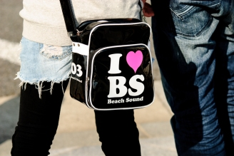 "A young Japanese girl carries a bag that states ""I Heart BS (Beach Sound"""